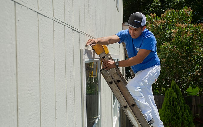 A Kelly Brothers Painting crewmember helps finish up painting a house in the Reno area.