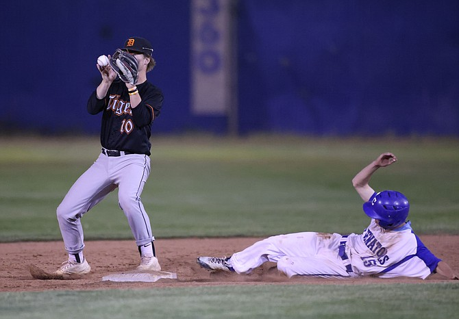 Carson's Aiden Lopez slides into second as Douglas' Luke Ackermann barehands the ball during the league game between the Carson Senators and the Douglas Tigers at Carson High School.
