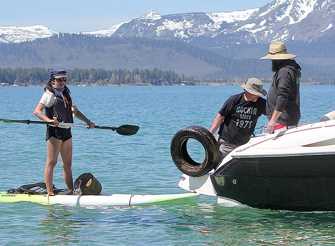 A volunteer fishes a tire out of Lake Tahoe as part of Friday's underwater clean-up.