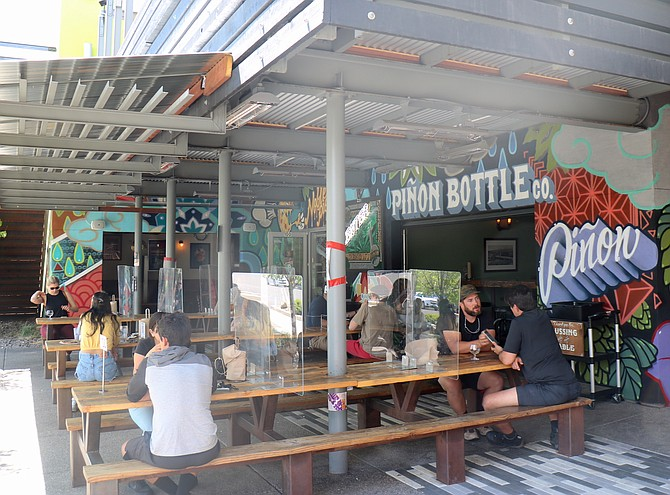 People drink outside on the patio of Piñon Bottle in mid-May 2021 in Reno's Midtown.