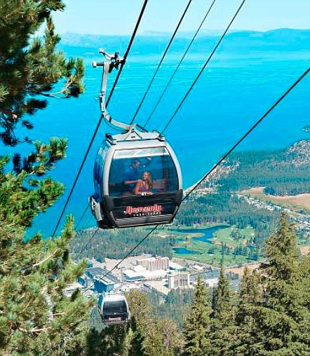 Sightseers take in the South Shore of Lake Tahoe while riding up the Heavenly Gondola.