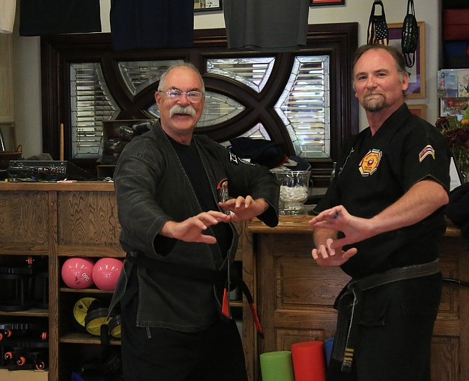 Kenpo karate instructor Jhan Yaple and fellow instructor Sean Morey pose for a photo inside of Yaples's Adult Kenpo Karate business.