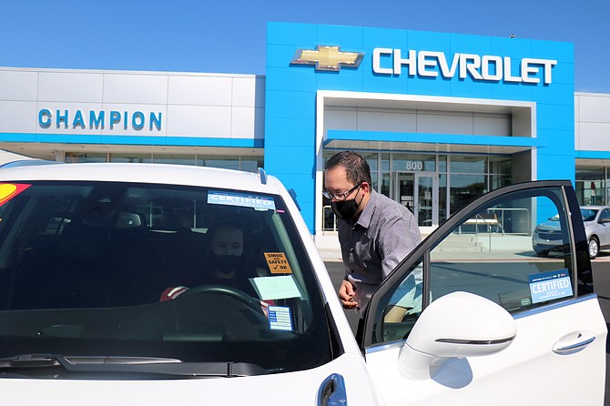 Kevin Lemus, fleet associate at Champion Chevrolet, shows a vehicle to a customer on Tuesday, May 25, at the dealership's lot at 800 Kietzke Lane in Reno.