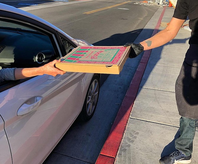 Aaron Foster, right, owner of Food + Drink in Reno's Midtown, hands off a pizza to a customer who ordered curbside pickup last spring. The restaurant, which opened in early 2020, has run on takeout orders throughout the pandemic.