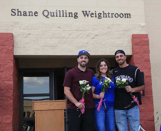 The Quillings pose in front of the 'Shane Quilling Weightroom' on Thursday as Carson High enshrined the name of their longtime weights coach on the room. From left to right are Shane Quilling's three children, Connor, Camryn and Chance. (Photo: Carter Eckl/Nevada Appeal)