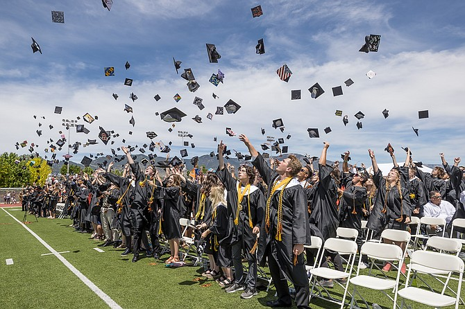 Douglas High School graduates launch their mortarboard caps into the wind on Saturday.