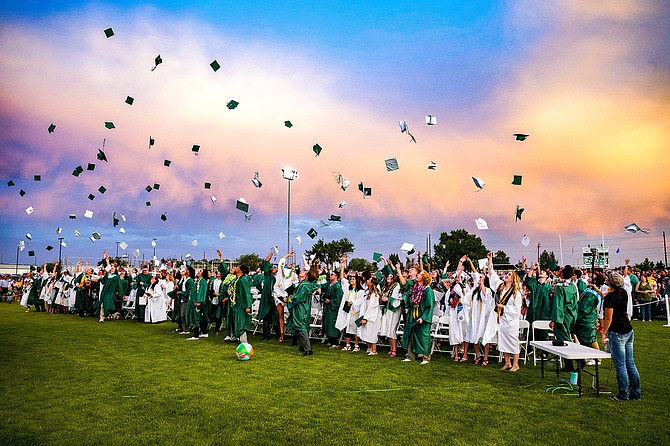 Students from the Churchill County High School Class of 2021 toss their caps at the conclusion of Friday's graduation ceremony at the Edward Arciniega Athletic Complex.