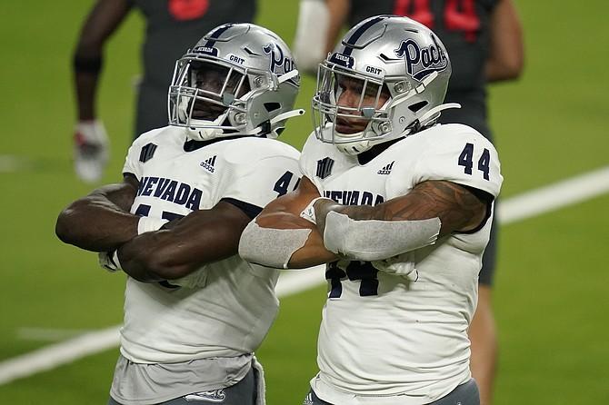 Nevada linebacker Trevor Price, left, and defensive end Daniel Grzesiak (44) celebrate after a play against UNLV on Oct. 31, 2020, in Las Vegas. (Photo: John Locher/AP, file)