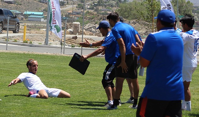 Battle Born FC's Chams 'James' Khelifi slides toward his bench after scoring a goal Saturday.