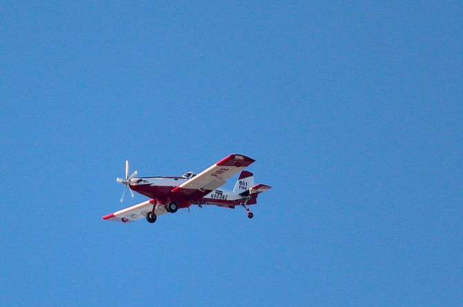 A firefighting aircraft flies over Indian Hills on Wednesday evening to battle the fire burning in Jacks Valley.