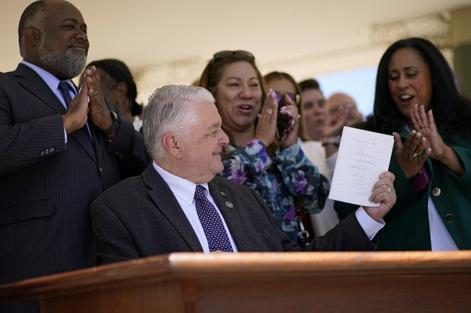 Nevada Democratic Gov. Steve Sisolak holds up a bill newly signed into law Friday, June 11, 2021, in Las Vegas. The law would make Nevada the first to vote on the 2024 presidential primary contests, though national political parties would need to agree to changes in the calendar or state parties could risk losing their delegates at presidential nominating conventions. (AP Photo/John Locher)