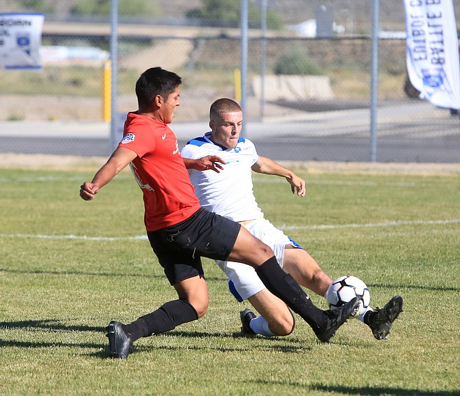 Battle Born FC defender Ben Mitcheson slides to compete for a ball with a Sierra Nevada FC forward Saturday evening. Mitcheson and the rest of the Battle Born FC defense now have gone two-plus matches without allowing a goal.