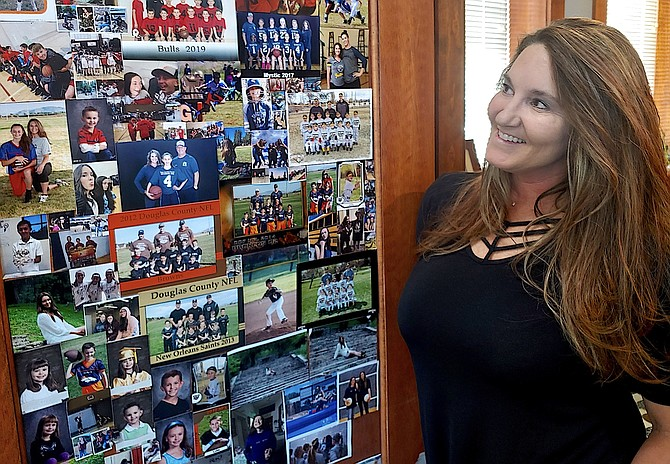 Executive Director of the Douglas County Chamber of Commerce Alicia Main stands next to a wall of photos of family and teams she has been involved in.