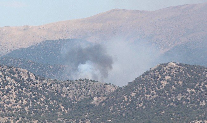 Smoke from a fire rises from the Pine Nut Mountains east of Stockyard Road
