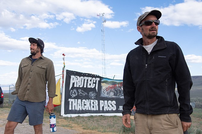 Environmental activists Will Falk, left, and Max Willbert, right, stand in front of the encampment on May 18, 2021. They have helped organize tribal members to oppose the mine.