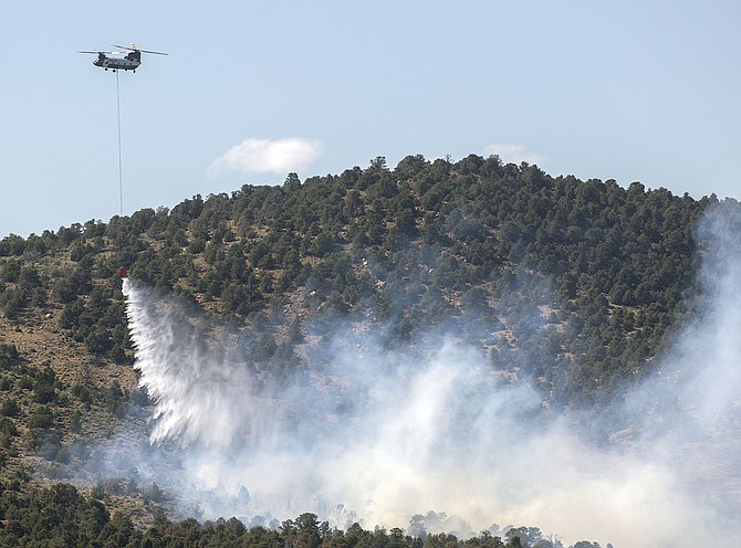 A helicopter drops water on the Mineral Fire in the Pine Nuts on Monday.