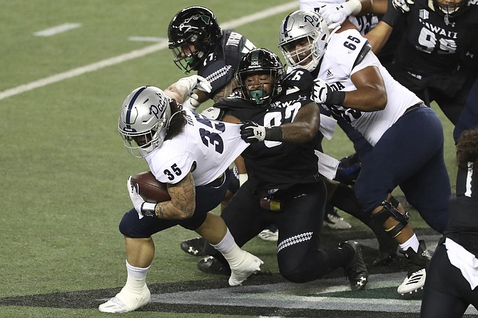 Nevada offensive lineman Aaron Frost (65) tries to keep Hawaii defensive lineman Zach Ritner (97) from pulling down Nevada running back Toa Taua (35) on Nov. 28 in Honolulu. (Photo: Marco Garcia/AP, file)