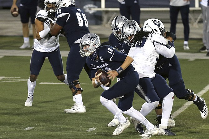 University of Nevada quarterback Carson Strong against Utah State on Nov.5, 2020, in Reno. With new rules concerning college athletes earning money, we could be seeing Strong's likeness all over Northern Nevada, Joe Santoro writes. (Photo: Lance Iversen/AP, file)