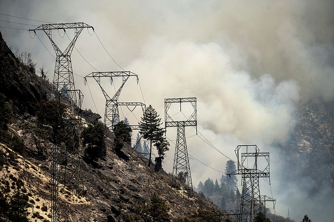 Smoke billows behind power lines as the Dixie Fire burns along Highway 70 in Plumas National Forest, Calif., on Friday, July 16, 2021. (AP Photo/Noah Berger)