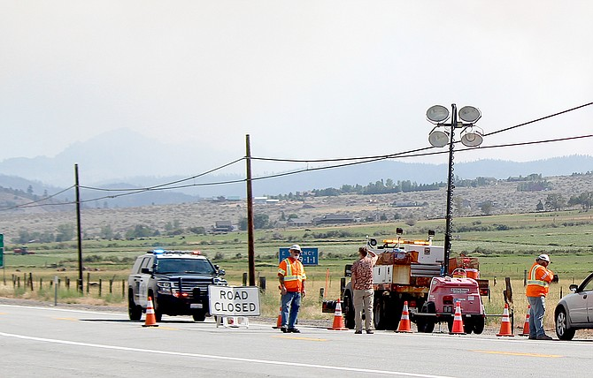 Cal Trans workers talk to a motorist at Highway 88 and the state line on Tuesday afternoon. Highway 88 was closed as the Tamarack Fire continues to expand.