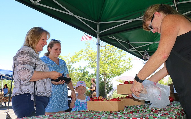 Sandy Torok, left, shops at Shirley's Farmers' Market in South Reno with her daughter, Molly, and granddaughter, Adalynn, on June 26, 2021. Torok is buying strawberries from Lisa Dermo, a seller for Rodriguez Farms, based in Watsonville, California.