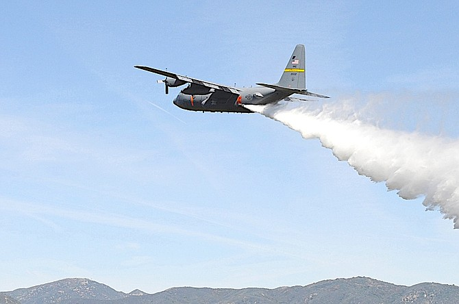 A Modular Airborne Firefighting System-equipped C-130 H assigned to the Wyoming Air National Guard drops a line of water during annual certification and training in 2016 near Channel Islands Air National Guard Station, Calif.