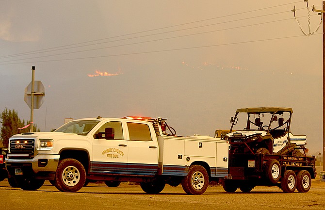 Storey County firefighters pull out of camp to fight the Tamarack Fire as flames are visible in the background