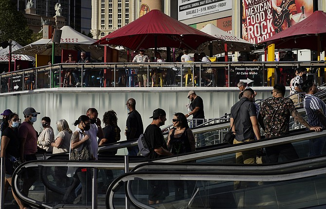 In this April 24, 2021, file photo, people walk as others dine on the Las Vegas Strip. (AP Photo/John Locher, File)
