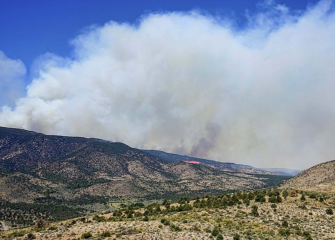 A pink stripe of retardant is dropped from a fire tanker at around 12:30 p.m. Wednesday in this photo by Topaz Ranch Estates resident John Flaherty. Smoke from the fire has increased, but aircraft are still able to fly.