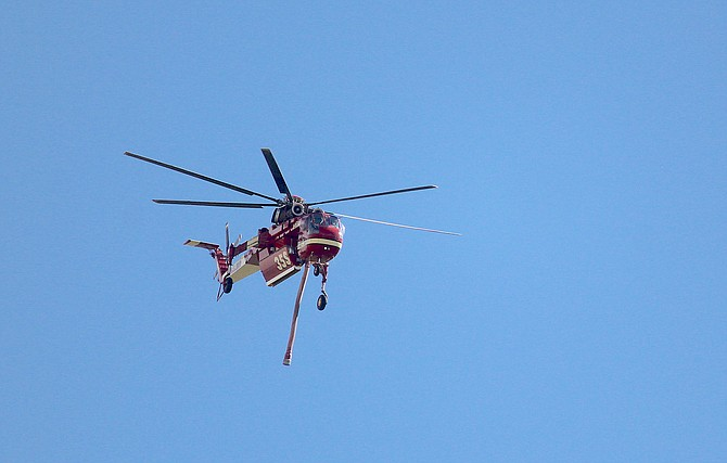 A firefighting helicopter returns from a drop on the Tamarack Fire near Woodfords.