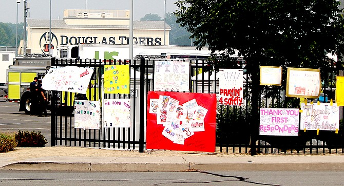 Signs thanking firefighters on Saturday and urging them to stay safe line the fence at Douglas High School where they are staged for the Tamarack Fire.