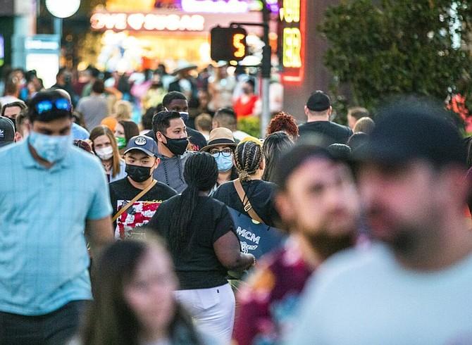 Pedestrians walk on the Las Vegas Strip on Saturday, March 27, 2021.