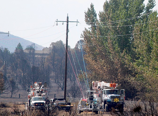 NV Energy linemen string wire just north of Holbrook Junction after a section of power poles and line was destroyed in the Tamarack Fire.