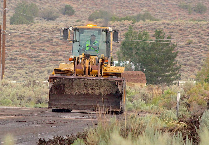 A Douglas County roadworker clears Jacobsen Lane in Fish Springs on Saturday morning.