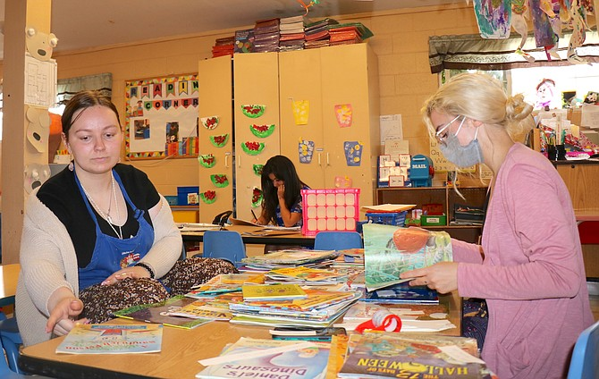 Teachers at Little Bear Preschool and Childcare in Sparks organize books for the children to read on Monday, July 19.