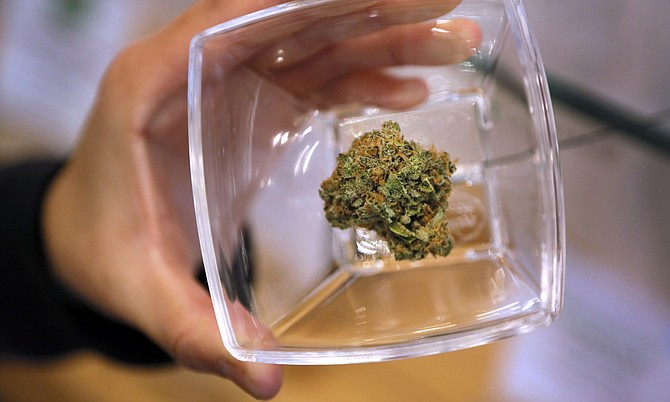 Patient advisor Sue Chung holds a jar containing a marijuana flower at The Source dispensary in Henderson on Thursday November 9, 2017.