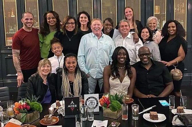 This photo provided by Sylvia Crawley Spann, shows former WNBA player Sylvia Crawley Spann and her husband Brian, seated bottom right, celebrating their wedding with Las Vegas Aces WNBA basketball team owner Mark Davis, standing at center, and other former members of the franchise and their guests at a restaurant in Las Vegas on May 29.