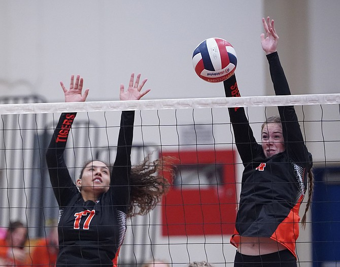 Douglas High's Addy Doerr, right, and Mia Bertolone, left, jump to block a Reno attack Thursday on the road. Reno volleyball swept the Tigers, 3-0, to open league play.