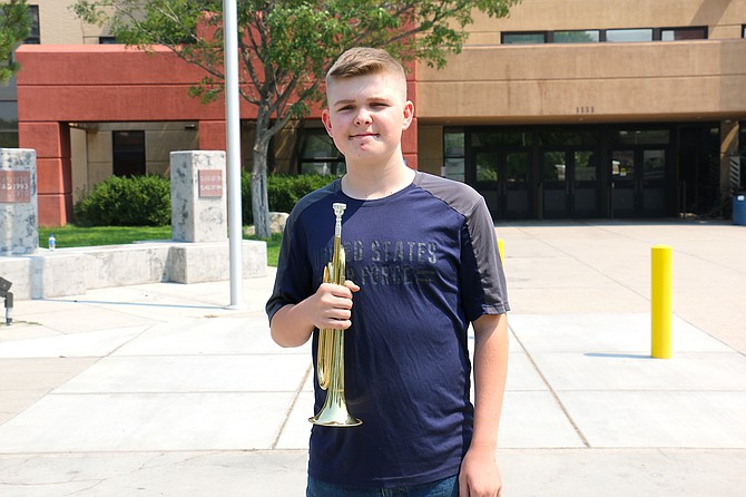 """Devin Linehan, Carson High School freshman, stands with his bugle outside the front of the school Monday. Linehan's performance of """"taps"""" Thursday to honor the U.S. service members who died in Afghanistan last week was recorded and posted, and the video since has gone viral on Facebook. (Photo: Jessica Garcia/Nevada Appeal)"""