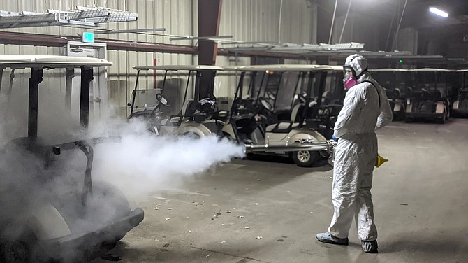 Chad Grayot, founder of Reno-based company Bio Sealed, uses a disinfecting fogging machine at a Duncan Golf Management golf cart storage facility in Reno.