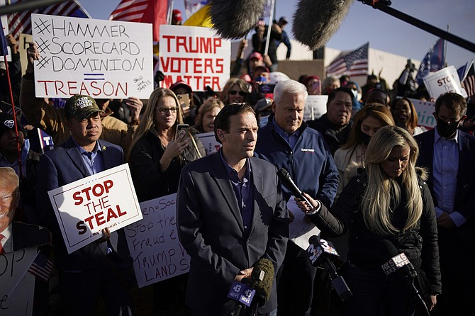 John Locher/AP, file Former Nevada Attorney General Adam Laxalt, middle speaking at microphone, and American Conservation Union Chairman Matt Schlapp speak during a news conference outside of the Clark County Election Department in North Las Vegas on Nov. 8, 2020.