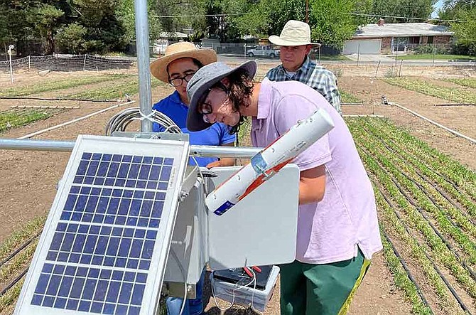 Doctoral student Uriel Cholula-Rivera and undergraduate student Jackson Zolmer connect an infrared thermometer measuring plant canopy temperature to a data logger as part of the irrigation research being conducted at the University's Experiment Station on Valley Road in Reno.