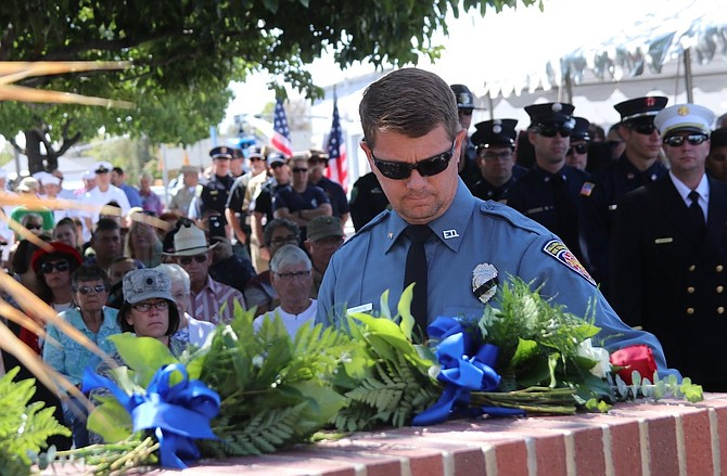 City of Fallon employee and volunteer fireman Gary Johnson places a rose at the on the city's 9/11 Memorial in 2019.
