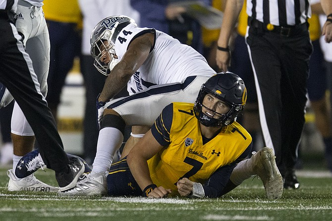 California quarterback Chase Garbers looks up after being sacked by Nevada defensive end Daniel Grzesiak on Sept. 4, 2021, in Berkeley, Calif. (AP Photo/D. Ross Cameron)