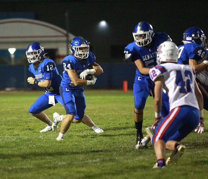 Carson High running back Wes Dunkin (24) takes a carry up the middle while playing at Reno High Friday night.