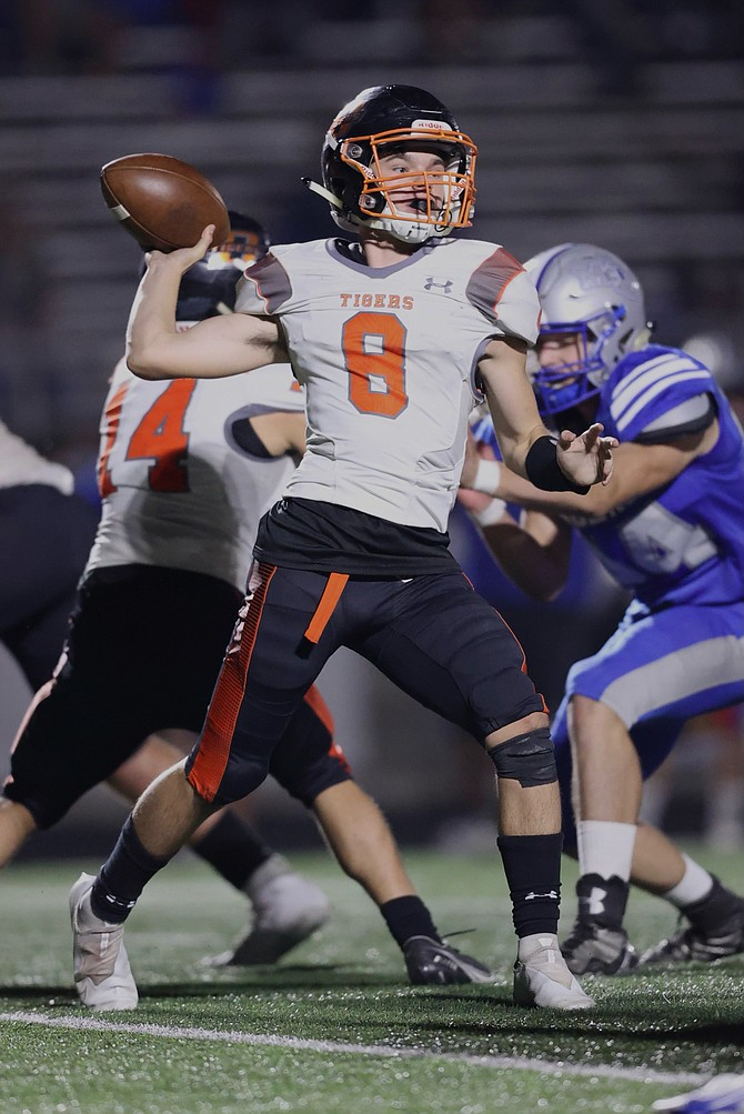 Sophomore quarterback Owen Evans winds up to throw a pass against McQueen last Friday. Douglas football is hoping to get its first home game of the season in Friday night against Reno.
