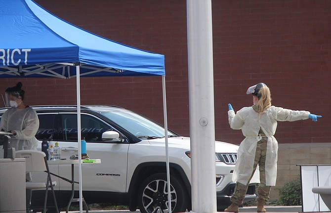 A member of the National Guard directs drive-through testing at the Douglas County Community and Senior Center on Thursday afternoon.