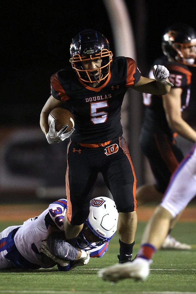Douglas High running back Robert Costello attempts to break free of a Reno tackler Friday night in Minden.