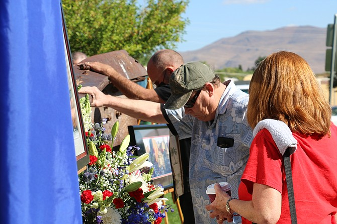 After speeches from city officials, Carson City residents took turns approaching the 9/11 memorial in Mills Park to touch the I-beam from the World Trade Center rubble. The beam was donated to Carson City in 2010 and dedicated in 2011.