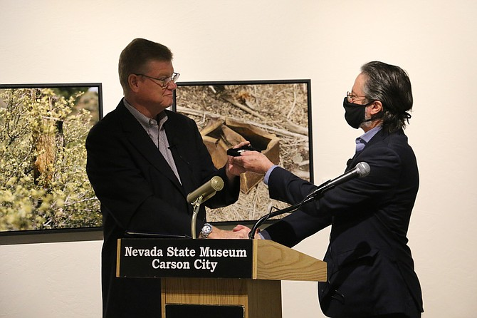 Rep. Mark Amodei presents the 2021 CC Morgan Dollar to Nevada State Museum Director Myron Freedman. After the speeches, audience members gathered around the silver dollar to take pictures. (Photo: Faith Evans/Nevada Appeal)